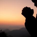 Foto de Silueta de niña orando sobre fondo de cielo hermoso.